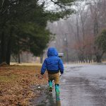 Toddler walking on side of road in rain. Photo by June Admiraal on Unsplash.
