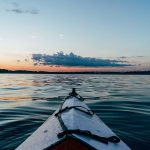 Photo of kayak on calm waters at sunset. Photo by Joshua Ness on Unsplash