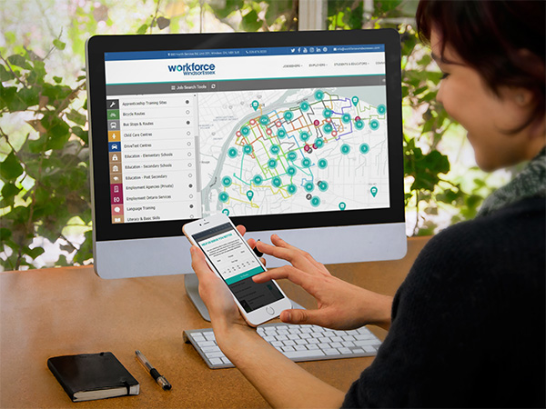 Woman using WEmap jobs board on phone in front of a large monitor featuring Wemap job board